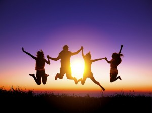 group of happy young people jumping on the mountain